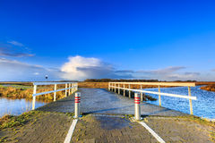 Bron över floden i ett lantligt landskap tände vid morgonsolen Royaltyfria Bilder
