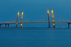 Bron av cirkelhuvudvägvägen över den Neva floden nära munnen av den i den blåa timmen efter solnedgången royaltyfri bild