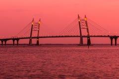 Bron av cirkelhuvudvägvägen över den Neva floden nära munnen av den i den guld- timmen under solnedgången royaltyfria foton