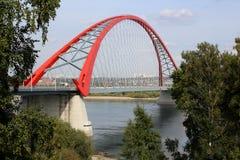 Bron med den röda bågen lokaliseras över rutten för stads- transport för floden arkivfoto