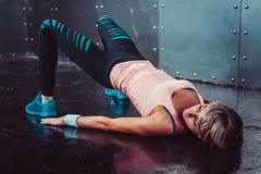 Bron poserar den sportiga kvinnan som gör konditiongenomkörare Arkivfoton