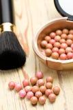 Broncear las perlas y el cepillo del maquillaje Fotos de archivo