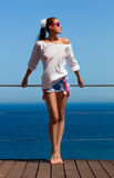 Bronced Brunette Girl in Denim Shorts. Beauty Long Legs. Fashionable bronced woman in denim jeans shorts with pink suspenders and white shirt Stock Image