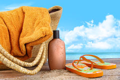 Broncee la loción, con la toalla en la playa Foto de archivo