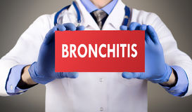 Bronchitis. Doctor`s hands in blue gloves shows the word bronchitis. Medical concept royalty free stock photos
