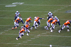 Broncos line protects manning. Peyton manning hands off behind a secure offensive line royalty free stock images