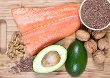 Bronnen van omega 3 vetzuren: flaxseeds, avocado, zalm en okkernoten Stock Foto