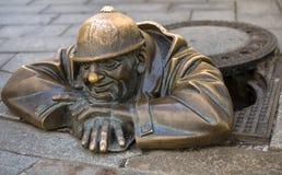 Brons beeldhouwwerk geroepen Cumil & x28; Watcher& x29; of Mens op het werk, Bratislava, Slowakije Stock Afbeeldingen