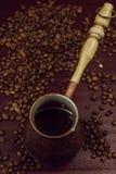 Brons kaffeturken och kaffebönor Bakgrund arkivfoto