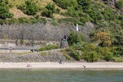 Brons skulptur av en sjöjungfru på foten av Loreleyen vaggar på bankerna av Rhen i Tyskland arkivfoto