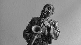 Brons statyetten av en man som spelar saxofonen royaltyfri fotografi