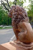 Brons statyn av ett modigt lejon på en sockel i parkera royaltyfri foto