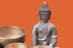 Bronsbeeldhouwwerk van Boedha op oranje achtergrond Royalty-vrije Stock Afbeelding