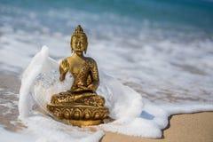 Bronsbeeldje Boedha op het strand met golven Stock Afbeelding