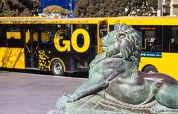 Bronslejonet på grunden av Wellington Cenotaph med staden bussar i bakgrunden Fotografering för Bildbyråer