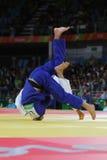 Bronsmedaljör Judoka Ryunosuke Haga av Japan i vit i handling mot Jevgenijs Borodavko av Lettland under match för män -100 kg Royaltyfria Bilder