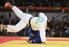 Bronsmedaljör Judoka Ryunosuke Haga av Japan i vit i handling mot Jevgenijs Borodavko av Lettland under match för män -100 kg Arkivfoton