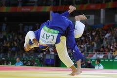 Bronsmedaljör Judoka Ryunosuke Haga av Japan i vit i handling mot Jevgenijs Borodavko av Lettland under match för män -100 kg Royaltyfri Fotografi