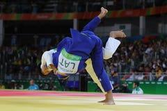 Bronsmedaljör Judoka Ryunosuke Haga av Japan i vit i handling mot Jevgenijs Borodavko av Lettland under match för män -100 kg Royaltyfria Foton