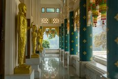 BronsrollbesättningBuddha avbildar i många åtgärdar i kloster av den sakrala korridoren för buddism av den Wat Pha Phu Gon temple arkivbild