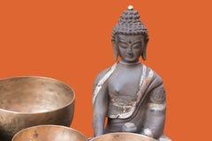 Bronsskulptur av Buddha på orange bakgrund Royaltyfri Bild