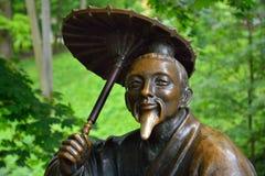 Bronsskulptur av kines med paraplyet nära arkivfoton