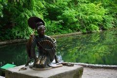 Bronsskulptur av kines med paraplyet nära royaltyfri bild