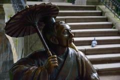 Bronsskulptur av kines med paraplyet nära fotografering för bildbyråer