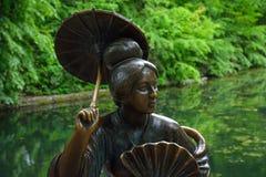 Bronsskulptur av kines med paraplyet nära royaltyfri fotografi