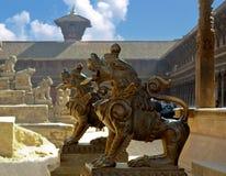 Bronsskulpturer av lejon framme av den Ganesh templet Royaltyfria Bilder