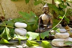 Bronsstandbeeld van het Raken van aarde Boedha met evenwichtige stenen Stock Afbeeldingen