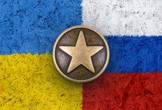 Bronsster op Oekraïense en Russische vlaggen op achtergrond Stock Foto's