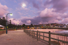 Bronte beach before sunrise with full Moon and city lights Stock Photos