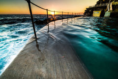 Bronte Pool at sunrise, Sydney, Australia. Bronte Pool, Sydney at sunrise with the orb of the sun just appearing over the horizon lighting up the rock pool as it stock photos