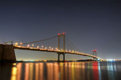 Bronx-Whitestone Bridge at Night. The Bronx-Whitestone Bridge reflecting on the East River at night in New York stock image