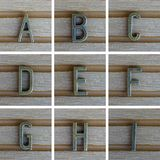 Bronz alphabet letter on wooden background. A, B, C, D, E, F, G, royalty free stock photo