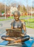 Bronz staty av barn som läser en bok Arkivbild