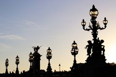 Alexandre III bridge Lamp posts Silhouettes at dusk in Paris france. The bronze Art Nouveau lamp posts that are located along the Pont Alexandre III bridge in stock images