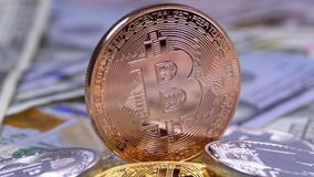 Bronze Bitcoin Coin, BTC and Bills of Dollars are Rotating. Different Crypto Currency Close-up. Macro. Dollar banknotes of various denominations on which lies stock video footage