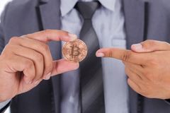 Bronze bitcoin in hand of business man. With suit stock photo