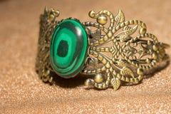 Bronze Bracelet with Malachite. Vintage ornamental bronze bracelet with big green stone malachite imitation royalty free stock image