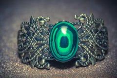 Bronze Bracelet with Malachite. Vintage ornamental bronze bracelet with big green stone malachite imitation royalty free stock photography