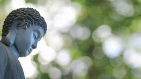 Bronze Buddha Sculpture in Traditional Sitting Meditation Pose on Bokeh Background