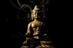 Bronze buddha in smoke isolated on black background Stock Photography