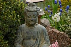 Bronze-Buddha-Statue im Garten mit Koniferenbäumen und Blumen Stockfotografie