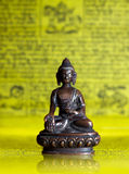 Bronze Buddha at Tibetan flags. Bronze Buddha sitting in padmasana at yellow Tibetan flags Royalty Free Stock Image