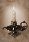 Bronze candlestick with burning candle. Photo shows the bronze candlestick with burning candle Stock Photography