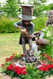 Bronze cast of the Mad Hatter pouring tea. Stock Images
