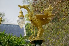 Bronze casting Thai literature swans carrying bell-shaped electricity lantern painted with gold colour stock image