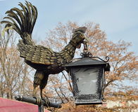 Bronze cock statue at the zoo. Garden decorations cock with lantern. Closeup Royalty Free Stock Photography